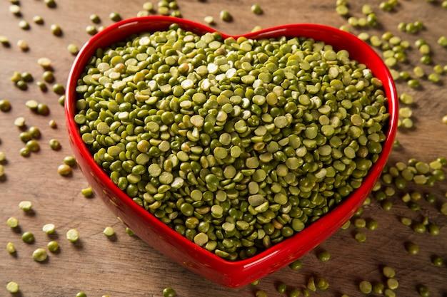 Lenticchie verdi all'interno di un vaso di cuore su uno sfondo di legno. legumi crudi commestibili della famiglia dei legumi.