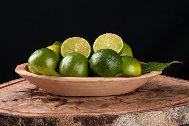 Frutto di lime verde in ciotola di legno e superficie nera.