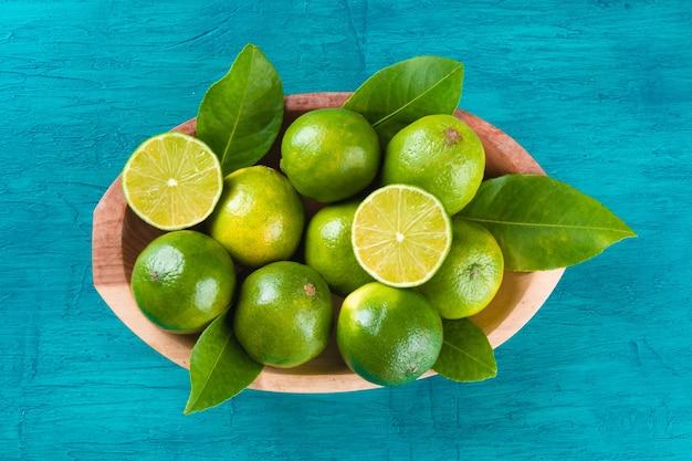 Frutto di lime verde in ciotola di legno sulla superficie blu.