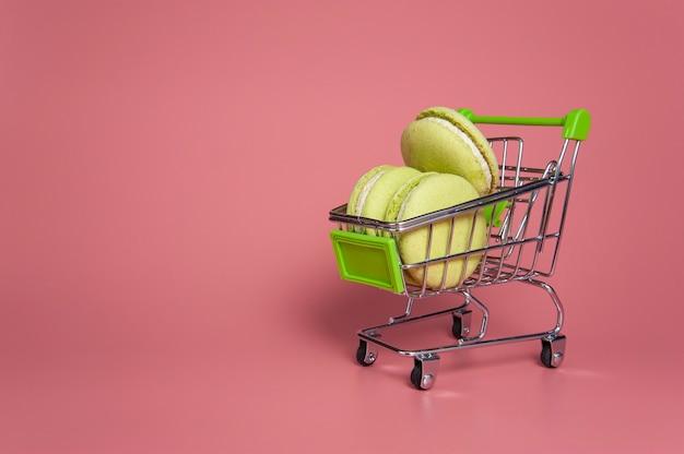 Macarons verdi in un carretto su sfondo rosa