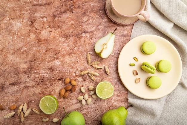 Macarons verdi o torte di amaretti con una tazza di caffè su una superficie di cemento marrone e tessuto di lino