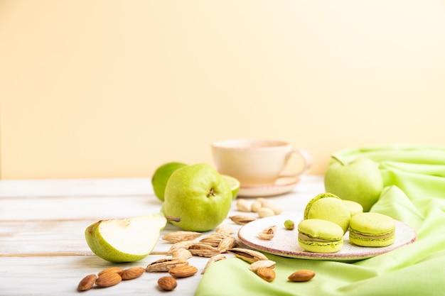 Macarons verdi o torte di amaretti con una tazza di caffè su una superficie bianca e arancione e tessuto di lino verde