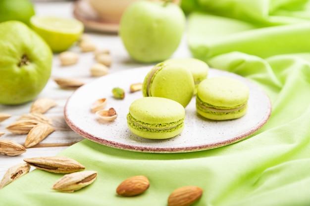 Macarons verdi o torte di amaretti con una tazza di caffè su un fondo di legno bianco e tessuto di lino verde. vista laterale, primo piano,
