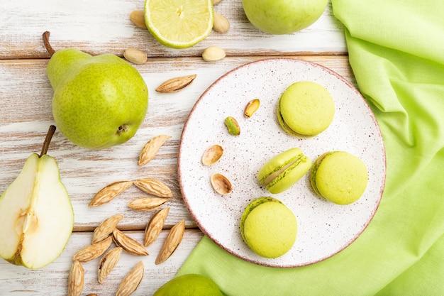Macarons verdi o torte di amaretti con una tazza di caffè su un fondo di legno bianco e tessuto di lino verde. vista dall'alto, piatto lay,