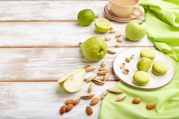 Macarons verdi o torte di amaretti con una tazza di caffè su una superficie di legno bianca e tessuto di lino verde
