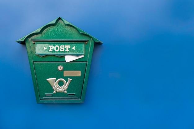 Cassetta postale verde con lettera attaccata all'interno su sfondo blu