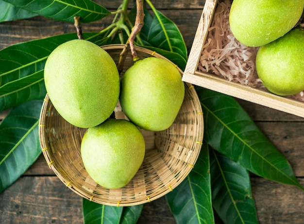 Merce nel carrello dei manghi verdi sul pavimento di legno