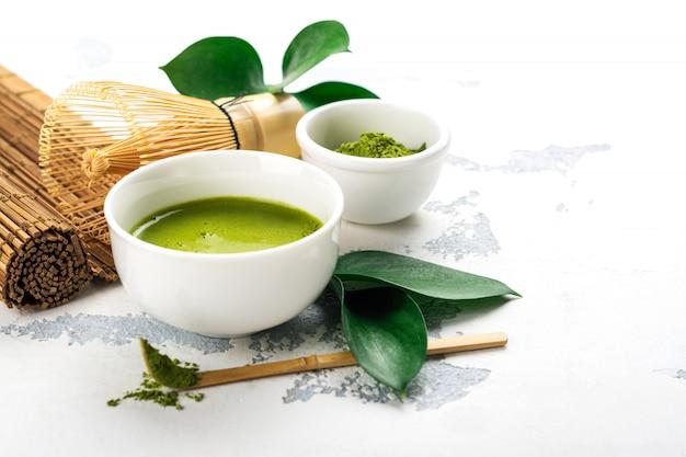 Bevanda verde del tè di matcha e accessori del tè su fondo bianco