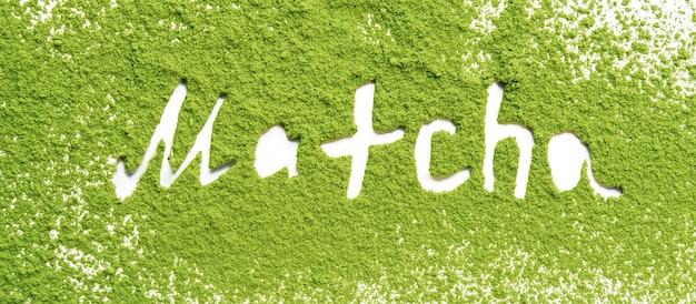 Tè verde matcha in polvere con scritte su sfondo bianco.
