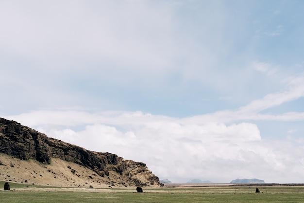 Un prato verde un campo per il pascolo del bestiame con erba sullo sfondo di montagne rocciose e