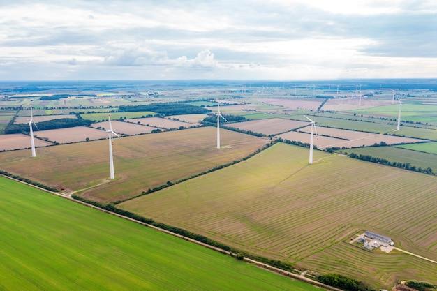Prato verde con turbine eoliche che generano elettricità, paesaggio estivo con cielo azzurro, fonti energetiche alternative