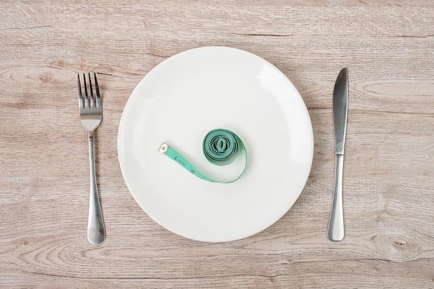 Nastro di misurazione verde avvolto intorno a forchetta e coltello con piatto in ceramica bianca sul fondo della tavola in legno