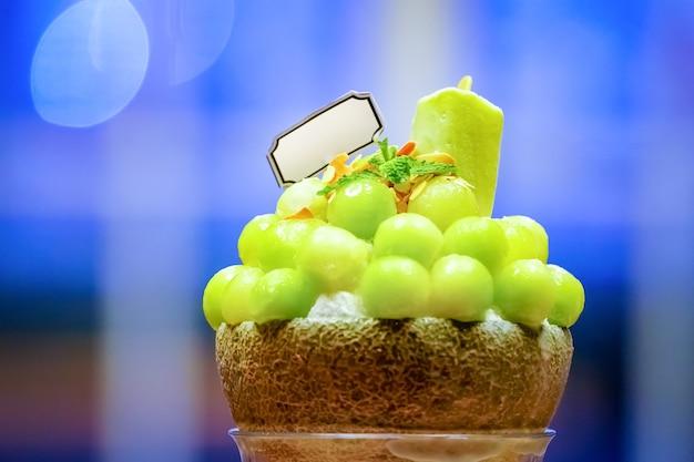 La forma della palla di melone verde è disposta sulla parte superiore del bingsu (stile gelato coreano) e decorata con gelato al tè verde e foglia di menta sul piatto di legno e latte condensato zuccherato accanto.