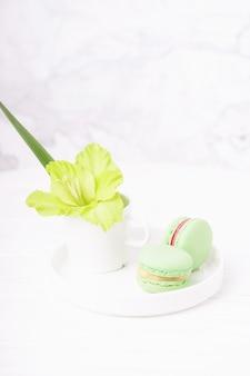Amaretti alla menta verde e fiore di gladiolo verde su sfondo di marmo bianco, spazio di copia