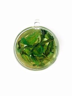 Tè verde alla menta in una tazza di vetro con foglie di menta su uno sfondo bianco isolato vista dall'alto