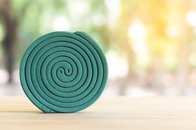 Repellente verde della zanzara sulla tavola di legno con la luce verde della sfuocatura.