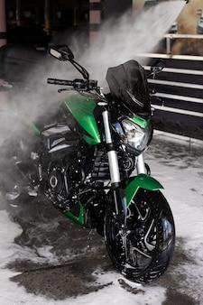Motocicletta verde all'autolavaggio sott'acqua