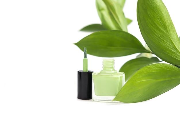 Bottiglia di smalto verde su superficie bianca.