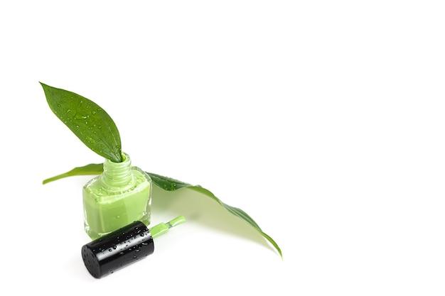 Bottiglia di smalto verde su superficie bianca. Foto Premium