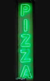 Insegna della pizza con luce al neon verde che segna un ristorante pizzeria
