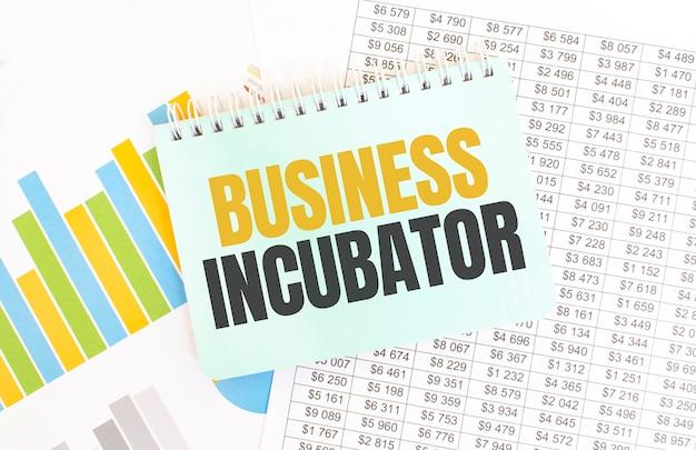Blocco note verde sulla documentazione finanziaria. testo incubatore di imprese. concetto di affari
