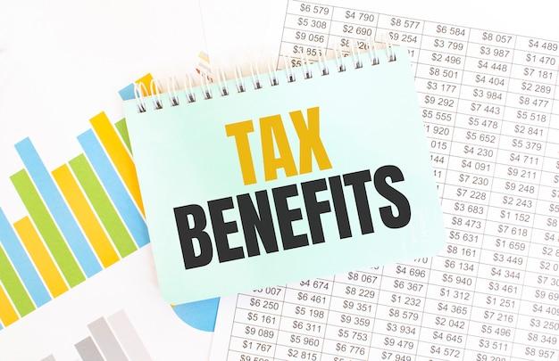 Blocco note verde sulla documentazione finanziaria. testo benefici fiscali. concetto di affari