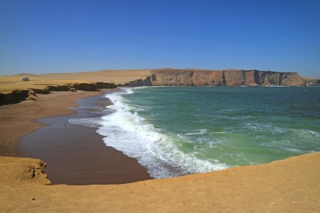 Oceano verde, spiaggia rossa, scogliera gialla e cielo blu alla riserva nazionale di paracas in ica, perù