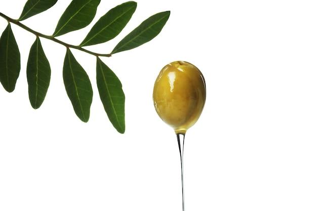 Oliva verde con olio isolato su superficie bianca