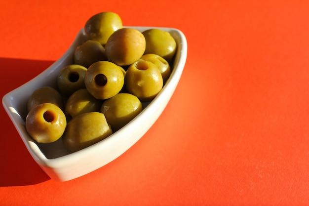 Olive verdi in un piatto bianco su sfondo rosso. cucina mediterranea.