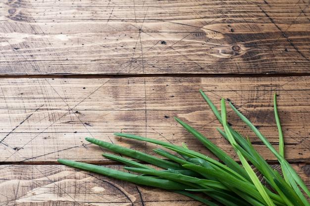 Cipolle verdi o scalogni su uno sfondo di legno