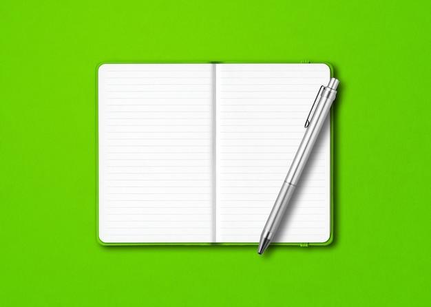 Mockup di taccuino a righe aperto verde con una penna isolata su sfondo colorato