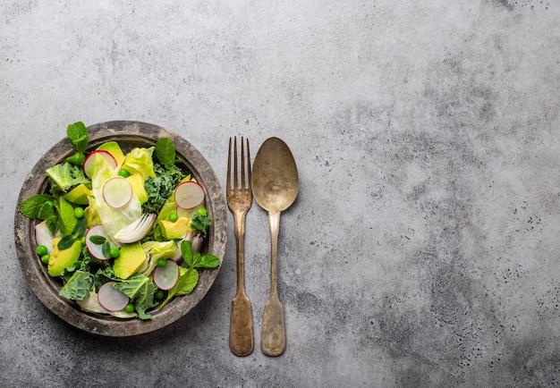 Insalata di verdure biologiche verdi con ravanello di erbe di piselli verdi di avocado in ciotola rustica