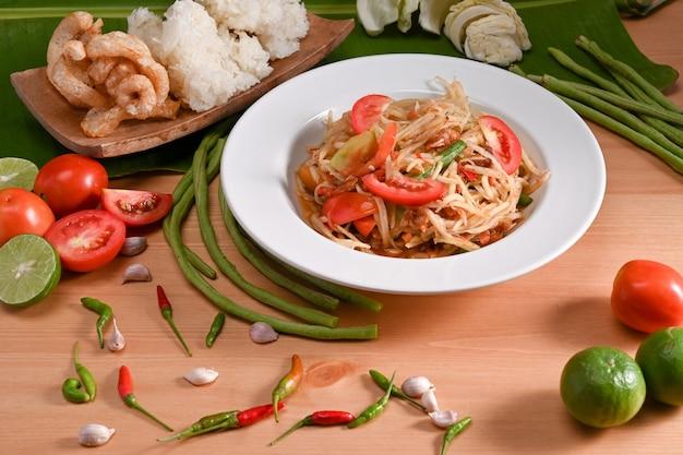 Insalata di papaia verde e ingredienti su fondo di legno. concetto di cibo tailandese.