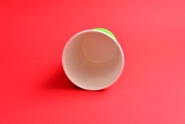 Tazza di carta verde su sfondo rosso. copia spazio.