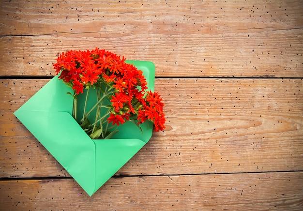 Busta di carta verde con fiori di lychnis rosso giardino fresco su sfondo di tavole di legno invecchiato. modello floreale festivo. progettazione di biglietti di auguri. vista dall'alto.