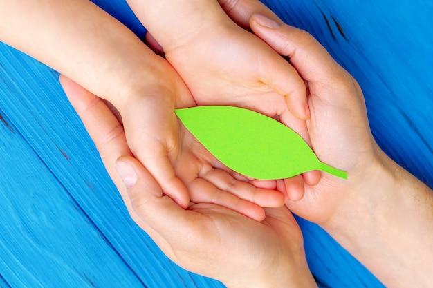 Foglia di carta verde nelle mani di adulti e bambini.