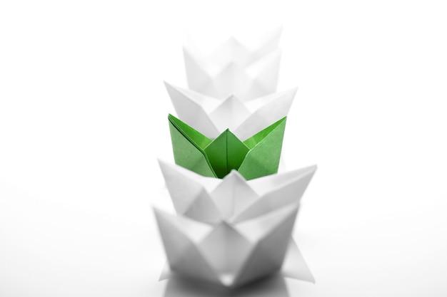 Nave di carta verde tra quelle bianche