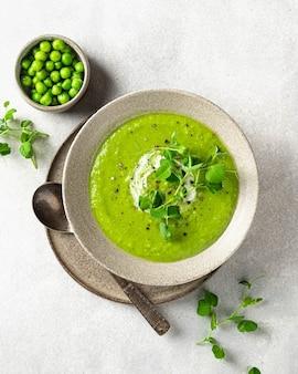 Zuppa di piselli verdi sulla vista superiore della superficie di cemento grigio