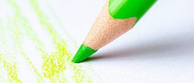 Una matita verde disegna tratti su carta bianca. copia spazio.