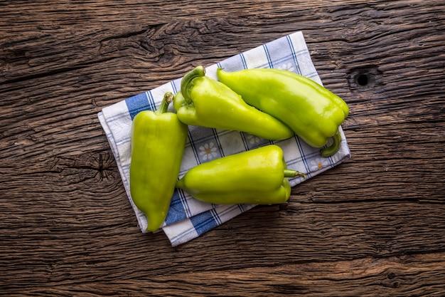 Pepe verde. tovaglia a quadretti blu del pepe verde fresco sulla vecchia tavola della quercia.