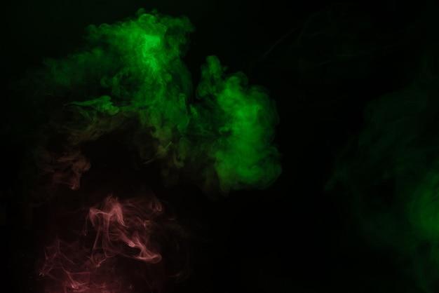 Vapore verde e rosa su una superficie nera. copia spazio.