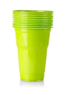I bicchieri di plastica verde su sfondo bianco. avvicinamento