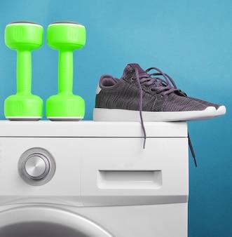 Manubri in plastica verde, scarpe sportive sulla lavatrice su sfondo blu