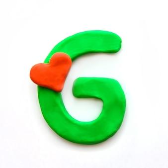 Alfabeto inglese lettera g di plastilina verde con cuore rosso che significa amore