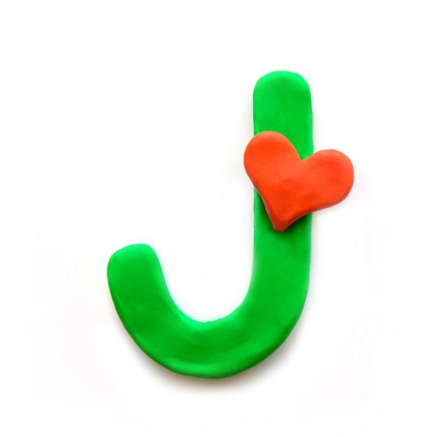 Alfabeto inglese lettera j di plastilina verde con cuore rosso che significa amore