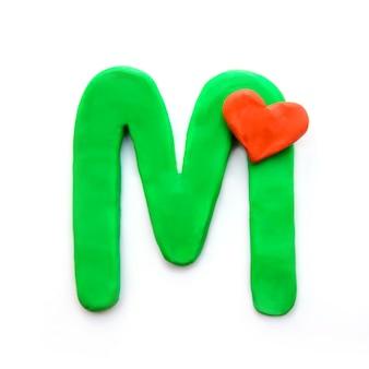 Lettera di plastilina verde m alfabeto inglese con cuore rosso che significa amore