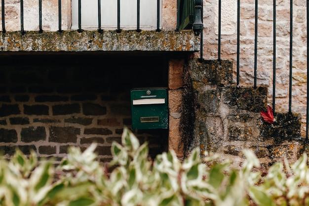 Cassetta postale verde sul muro di pietra sotto le scale. foto di alta qualità
