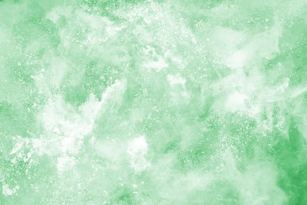 Esplosione di polvere verde su sfondo bianco
