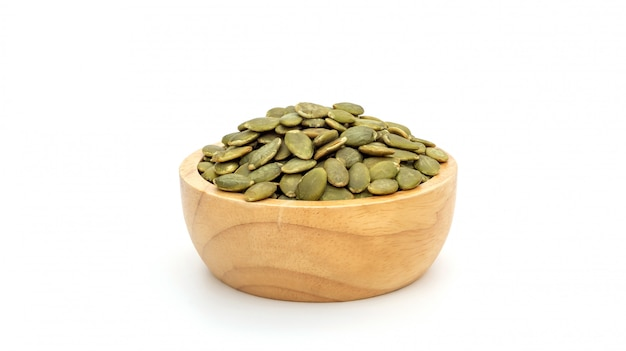 Semi di zucca verdi in una ciotola su una priorità bassa bianca.