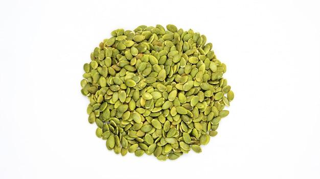 Semi di zucca verdi su una priorità bassa bianca